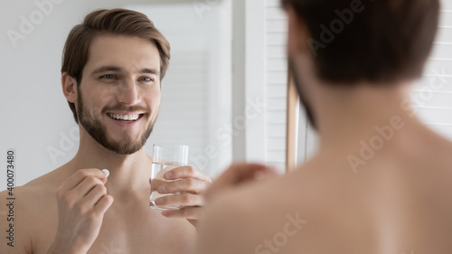 Fototapeta Head shot close up smiling young man looking in mirror, holding glass of water and pills, taking morning medicine or healthcare vitamins, improving immunity every day, feeling healthy and energetic. obraz na płótnie
