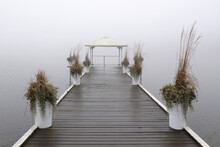 Romantic Moody Scenery With Wooden Pier With White Gazebo By Lake On Calm Misty Day