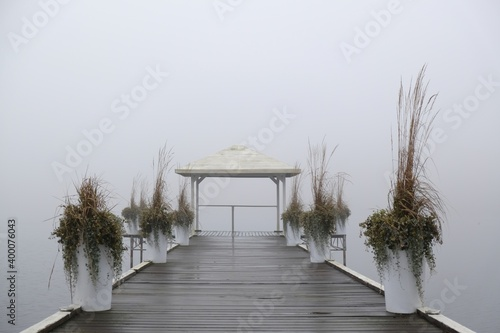 Fotografie, Obraz Romantic moody scenery with wooden pier with white gazebo by lake on calm misty