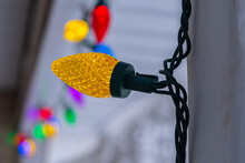 Closeup Of Brightly Colored Christmas Lights Strung From Railing Of Porch On House For Holiday