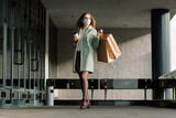 Fototapeta Uliczki - Young female wearing a mask for prevent virus with shopping bags on narrow street in Europe.