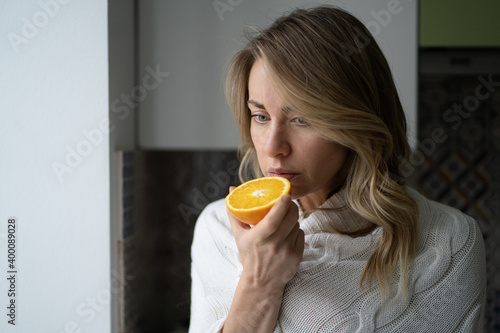 Fototapeta Sick woman trying to sense smell of  half fresh orange, has symptoms of Covid-19, corona virus infection - loss of smell and taste. One of the main signs of the disease.  obraz