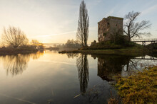 Remains Of Nijenbeek Castle In The Netherlands Along The River IJssel At Sunrise Reflecting In The Clear Still Swampland Water In The Foreground