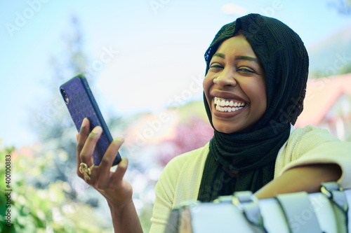 Obraz na plátně african woman using smartphone wearing traditional islamic clothes