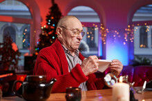 Bald And Serious Elder Man Sitting At Table And Holding A Letter In Cosy And Decorated Room With Christmas Tree.