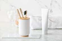Holder With Wooden Toothbrushes And Toothpaste On Table In Bathroom