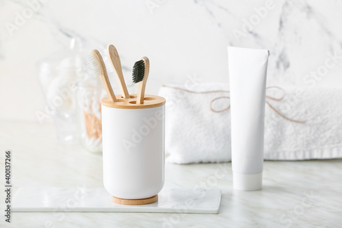Holder with wooden toothbrushes and toothpaste on table in bathroom Fototapeta