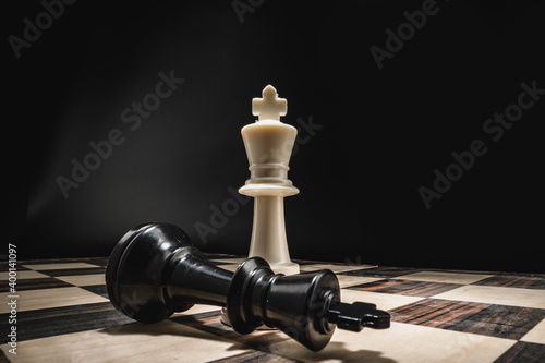Fotografiet Chess board with figures on dark background