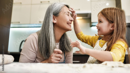 Fotografija Smiling little granddaughter smearing grandmother with flour