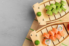 Avocado Sushi Roll And Roll With Salmon Served On Wooden Plates