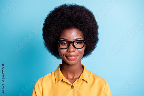 canvas print motiv - deagreez : Photo of dark skin big volume hairdo woman smiling straight nice calm look camera cute lovely face optics shop costumer wear eyeglasses yellow shirt isolated blue color background