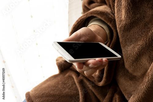 温かい恰好でスマートフォンを使う男性 Fototapet