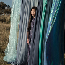 Portrait Of A Girl In A Dress Standing Outside Between Blue Sheets And Drapes On Laundry Line