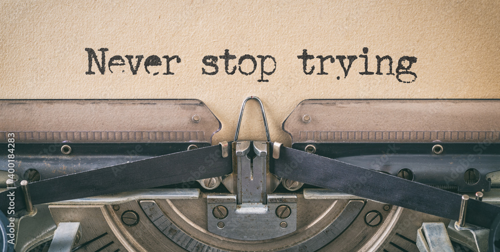 Fototapeta Text written with a vintage typewriter - Never stop trying