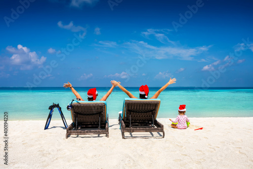Fotografie, Tablou A happy family wearing santa claus hats sits in sunbeds on a tropical beach and