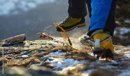 Fotografía Crampons and climbing boots, climber takes off crampons after the passage of the route in the winter mountains, climbing equipment close-up