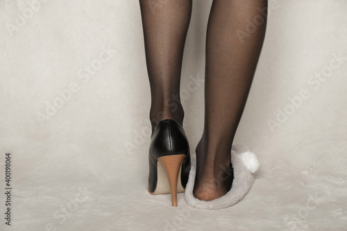 Valokuvatapetti female legs in black nylon tights and one leg in a warm indoor slipper and the o