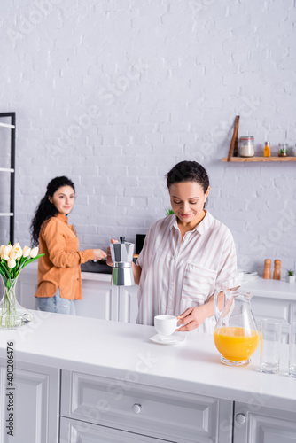 Obraz na plátne Hispanic lesbian woman holding coffeemaker near orange juice and partner on blur