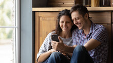 Happy Millennial Couple In Love Sit On Warm Floor At Kitchen Embrace Looking On Cellphone Screen. Young Husband And Wife Watch Photos On Phone Remember Sweet Moments Of Marriage Romantic Relationship