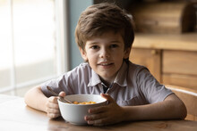 Best Breakfast Ever. Portrait Of Adorable Little Boy Looking At Camera Having Healthy Tasty Snack. Small Kid Posing By Kitchen Table Holding Bowl Of Sugar Coated Cereal Frosted Corn Flakes With Milk
