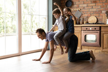 Ahead On Horse. Caring Young Father Giving Horseback Ride To Little Daughter Son Playing At Home On Weekend. Cute Brother Sister Kids Sitting On Back Of Dad Crawling Around On Kitchen Wooden Floor