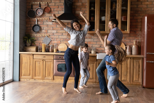 Fototapeta Barefoot dances. Overjoyed millennial family with little daughter son having fun listening to music dancing. Active mom dad and two junior school age kids jump at kitchen celebrate moving to new home obraz