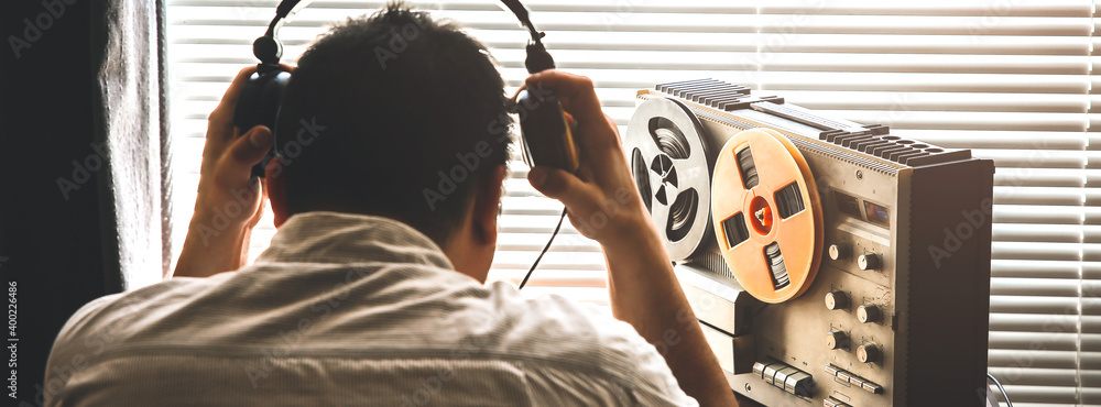 Fototapeta Special agent listens on the reel tape recorder. Officer wiretapping in headphones. KGB spying of conversations. Listen to music, retro hipster vintage radio.