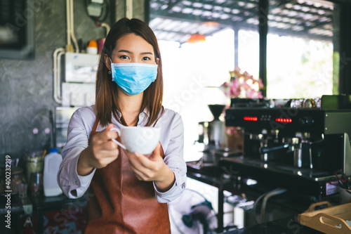 Fototapeta New normal startup small business Portrait of Asian woman barista wearing protection mask stand in her coffee shop reopening after lockdown obraz