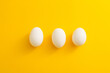 canvas print picture - three white eggs on a yellow background