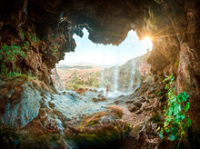 Image Inside A Cave With A Waterfall And The Silhouette Of A Man Opening His Arms. The Essence Of Freedom, A Sunset Inside A Cave With A Waterfall. Waterfall In Spain. Under The Water Of A Waterfall