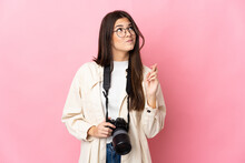 Young Photographer Brazilian Girl Isolated On Pink Background With Fingers Crossing And Wishing The Best