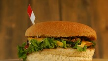 Delicious Burger With Small Singaporean Flag On Top Of Them With Toothpicks. Yummy Hamburger Rotating.