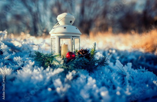 Fototapeta fabulous festive christmas card a candle burns in an elegant spruce wreath stands in the New Year's garden among the snow obraz