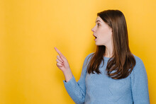 Excited Young Female Pointing Finger At Copy Space Surprised By Unbelievable Sale, Amazed Happy Brunette Girl Indicating Advertising Cheap Offer, Wears Sweater, Isolated On Yellow Studio Background