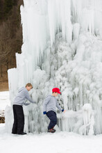 Young Children Play Together Outdoor, Next To An Ice Christmas Tree, Frozen Waterfall Like Natural Sculpture.