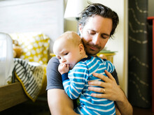 Father Embracing Baby Boy (12-17 Months) In Bedroom