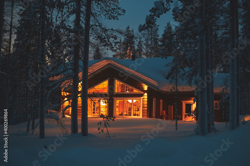 Fotografia A night view of cozy wooden scandinavian cabin cottage chalet house covered in s