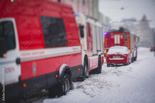 Fototapeta Group of fire men in uniform, firefighters with the fire engine truck fighting v