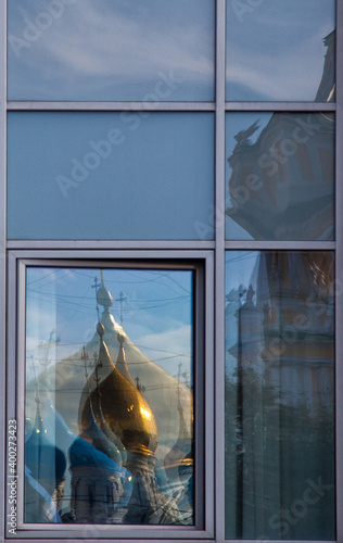 Reflection of the domes of the temple in the window of a modern building Fototapeta