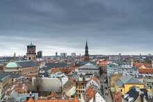 Aerial View Of Old Downtown Of Copenhagen City From The Round Tower (Rundetaarn) In Rainy Misty Day With Cloudy Sky With Red House Roofs And Church Of Our Lady (Vor Frue Kirke) And St. Peter's Church