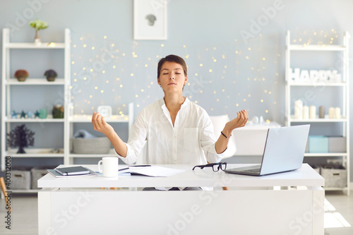 Tired woman sitting in office practicing meditation technique for concentration Fotobehang