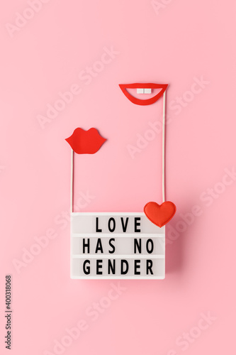 Lightbox with text LOVE HAS NO GENDER, red paper lips props on pastel pink background. Concept Homosexuality, lesbian love. Top view, creative flat lay. Holiday Greeting card. Vertical orientation