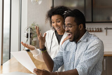 Happy Young African American Couple Feel Euphoric Read Good Unbelievable News In Paper Letter Correspondence. Overjoyed Biracial Man And Woman Triumph Get Pleasant Message In Paperwork.