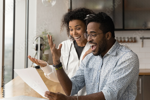 Obraz Happy young African American couple feel euphoric read good unbelievable news in paper letter correspondence. Overjoyed biracial man and woman triumph get pleasant message in paperwork. - fototapety do salonu