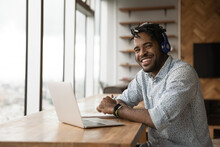 Portrait Of Smiling Young African American Man In Headphones Talk On Video Call On Laptop. Happy Millennial Biracial Male In Earphones Have Webcam Digital Virtual Conference On Computer Online.