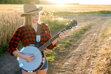 A Country Girl With A Banjo Stays In A Field