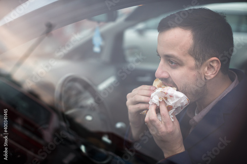 Fotografía Handsome young man eating a hurried lunch in his car (color toned image; shallow