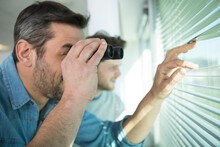Young Man Is Spying His Neighbours With Binoculars