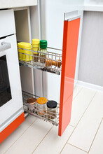 Upscale Maple Red Kitchen Spice Rack Drawer Vertical Cabinet With Mill Jars Of Spices And Groceries. Pull Out Spice Rack Cabinet Filler Pantry. Vertical Drawer With Orange Front Wooden Panel.