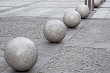 Row Of Glossy Granite Balls Decorative Traffic Barrier On The Pedestrian Sidewalk Paved With Square Stone Tiles, Cityscape Urban Street Architecture Details, Nobody.